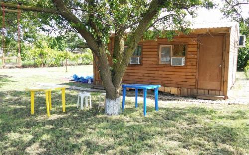 Домик, двухместный эко, отдельный вход, тв, кондиционер. Вид снаружи, напротив свой столик, стулья, мангал. Санузел напротив дома.